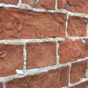 Spooled bricks due to application and removal of cement render